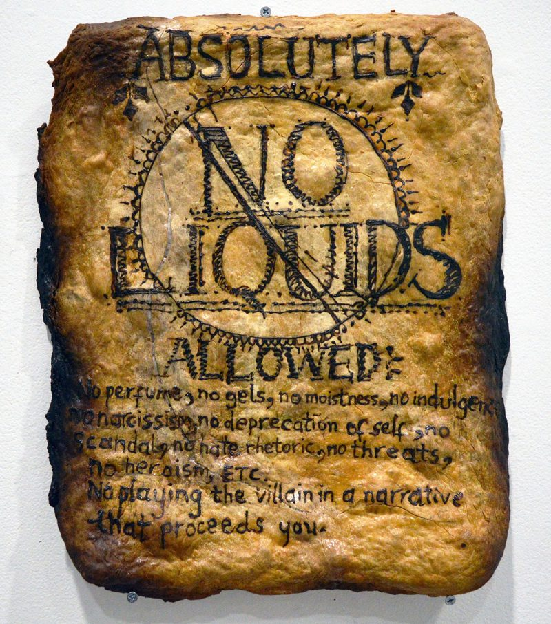 "Airport security sign, reads: -  Absolutely No Liquids Allowed: No perfume, no gels, no moistness, no indulgence, no narcissim, no deprecation of self, no scandal, no hate rhetoric, no threats, no heroism, ETC. No playing the villain in a narrative that precedes you.""  (Materials: Bread and henna)"